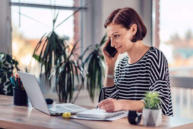 Mujer teletrabajando en un escritorio limpio y bien iluminado